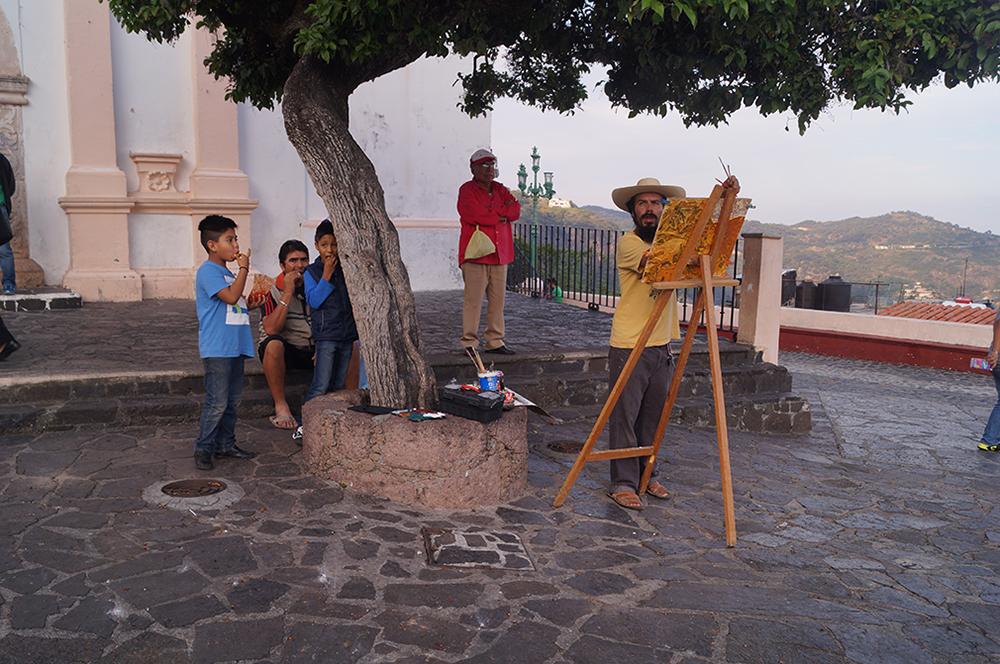 La locación elegida para el Barrio de Guadalupe fue el atrio de su iglesia, un espacio público que además resulta ser de los mejores miradores que tiene la bella ciudad de Taxco. Se encuentra a una gran altura, el proceso de construcción de la sesión de dibujo de paisaje se desarrolló en dos sesiones, el domingo 22 y el martes 24 de octubre, en estas dos sesiones se hicieron presentes los sonidos del barrio, las campanas, los cantos y el sermón de la misa, junto con las miradas de los habitantes y turistas. La segunda sesión resultó ser suculenta en tanto la sesión de dibujo de paisaje transcurrió con performance incluido –en torno a las Naciones Unidas, niños de kínder se reunieron para realizar la ceremonia en la plaza– y con la compañía de los niños de la primaria contigua que se acercaron como espectadores de la sesión. Fotografía del archivo del autor.