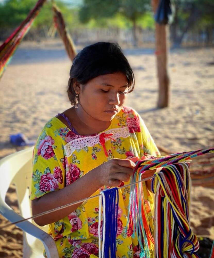 Mujer indígena Wayúu tejiendo. Imagen cortesía de @indigenadecolombia. La Guajira, Colombia. 30 de agosto, 2020.